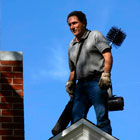 chimney sweep standing on the peak of a roof