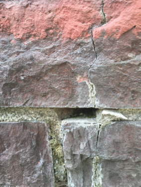 Weathered, cracked bricks that have missing mortar.