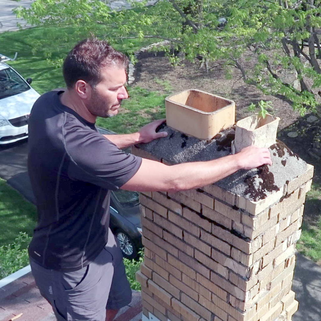 A man inspects a crumbling chimney.