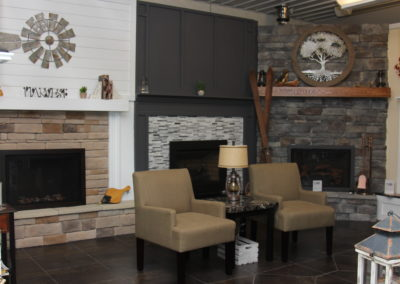 Several decorated fireplaces in a showroom with a sitting area.