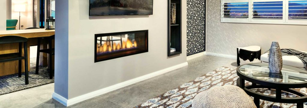 A see through fireplace in a living room area with an inbuilt bookcase and accent wall.