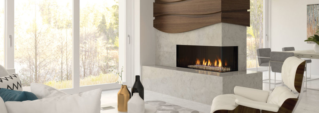 A corner fireplace in a living room area inside a wall feature helps separate this bright room.