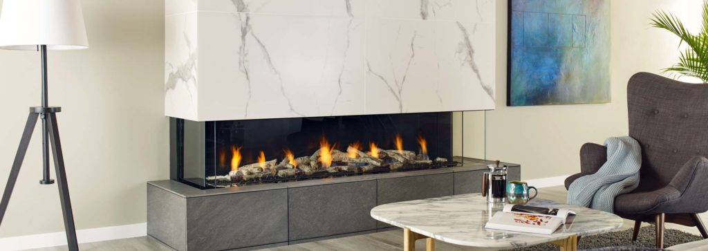 A three sided fireplace in a modern living space.